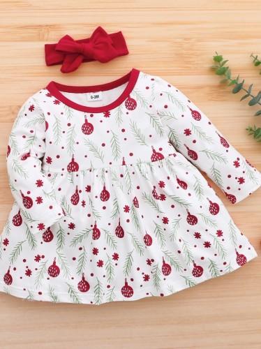 女の赤ちゃんは、ヘッドバンドが一致する白い長袖スケータードレスをプリント