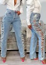 Jeans alla moda strappati ai lati della vita alta blu di estate