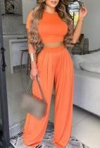 Комплект летнего формального кроп-топа оранжевого цвета и свободных брюк с высокой талией